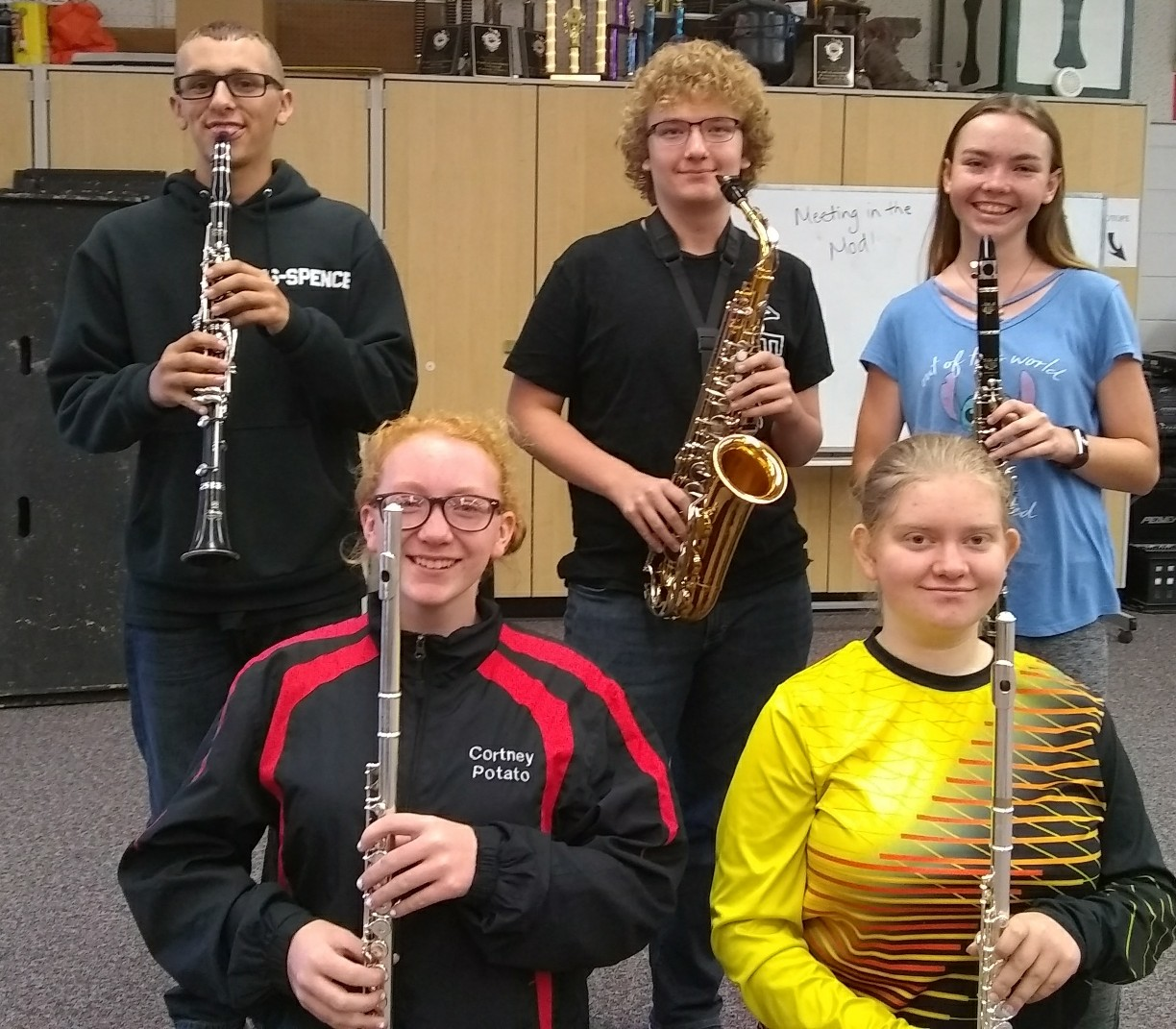 Spencer Carranza, Timur Brainard, Shaylin Prickett, Cortney McCausey, and Alexis Williams holding their instruments in the Highland band room after band class.