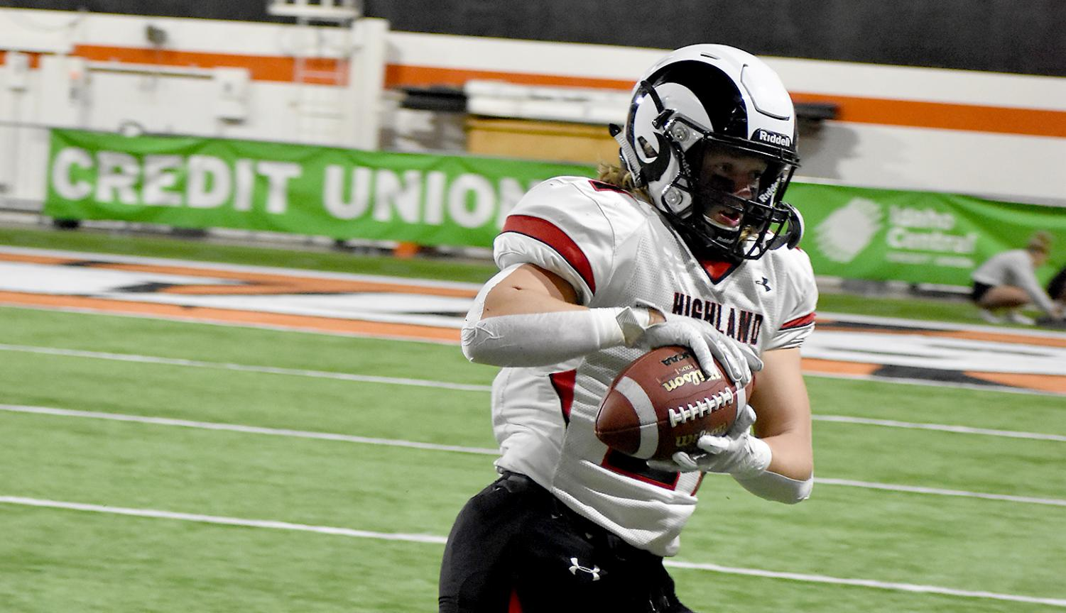 Running Back Kaleb Demuzio (grade 11) catches the ball and rushes downfield to get a first down and more at the Black and Blue Bowl, the annual battle against Pocatello High School.