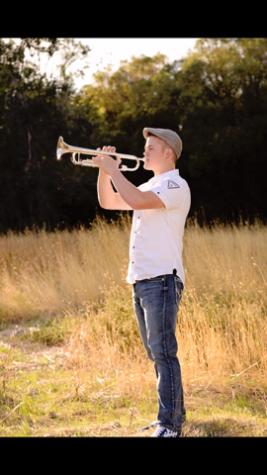 Trenton Brown poses for a Senior photo with his trumpet.