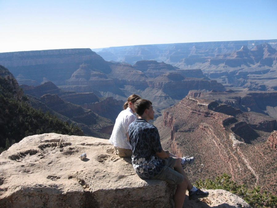 Mrs. Carlson travel companions sit at the Grand Canyon.
