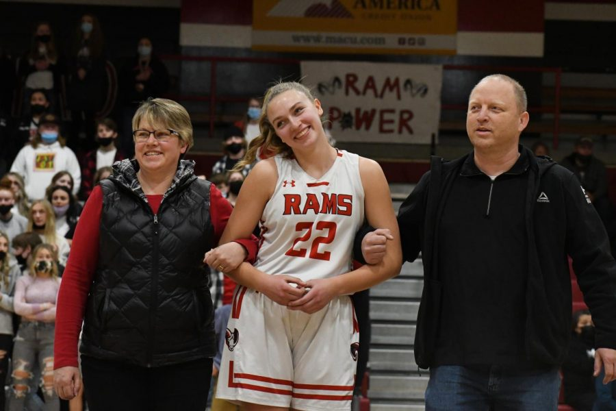 Lydia Maughan walks with her parents Kellie & Todd Maughan on senior night.