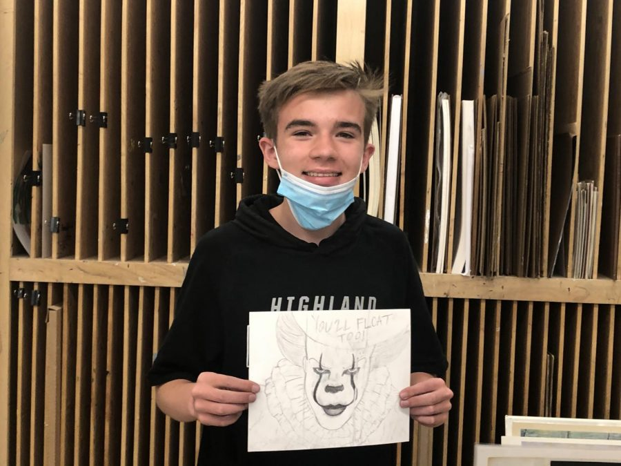 Tanner Crowder holding up his triptych of IT in Drawing 1, C33